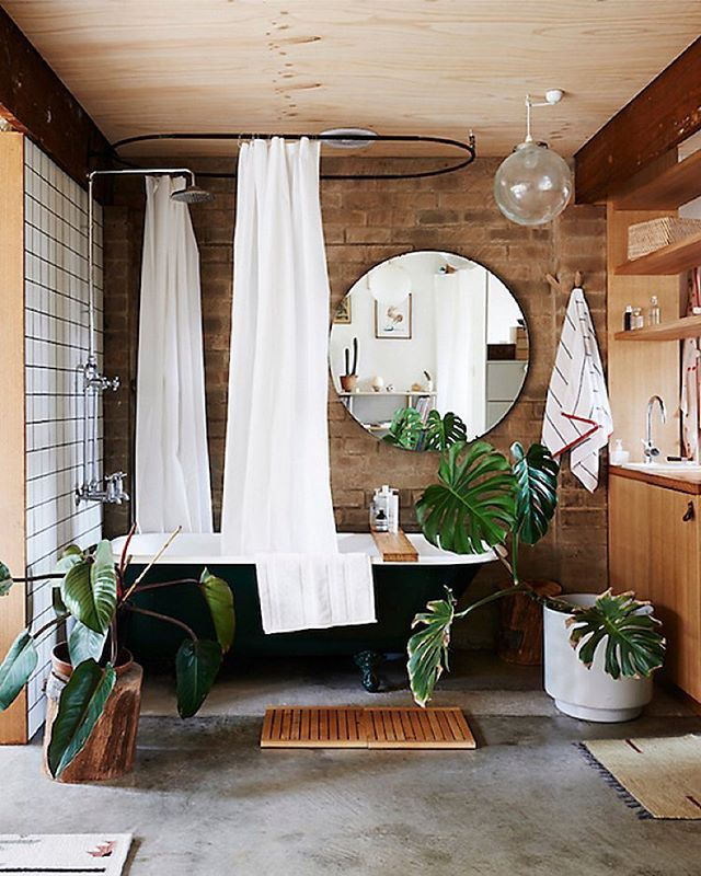Spa bathroom, oversized round mirror, wood details, black claw foot ...