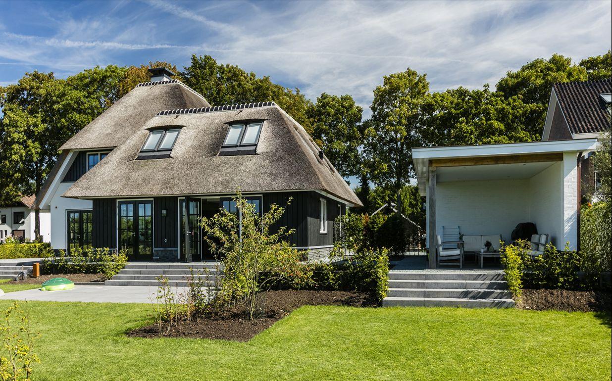 Achtergevel rietgedekte villa met overdekt terras achter de garage