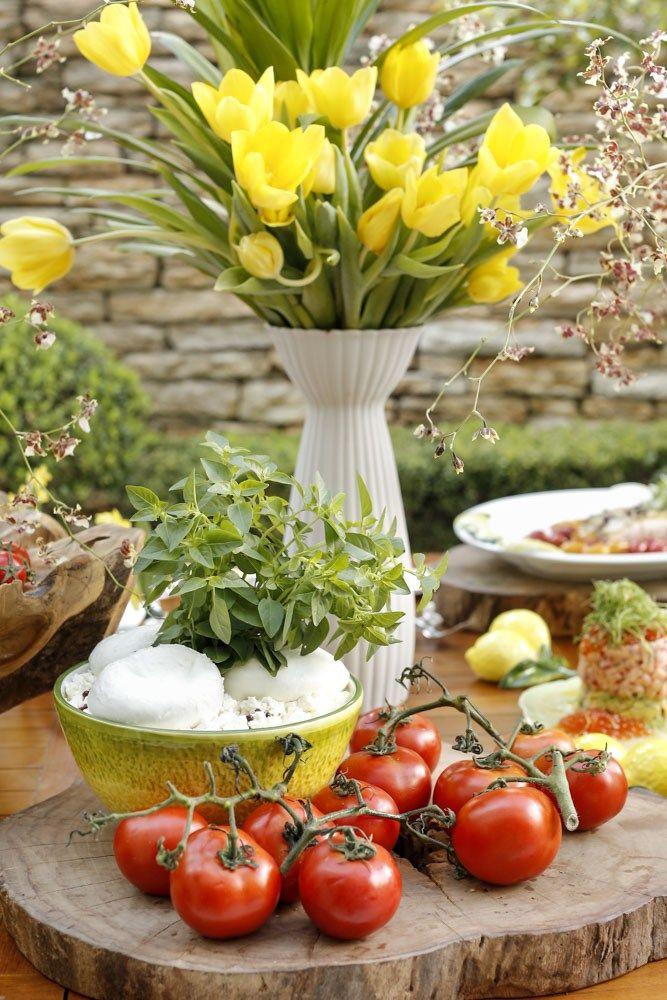 Decoramos a mesa oval usada como buffet com arranjos florais mais altos e soltos, também feitos por Marcinho da Milplantas, com orquídeas, tulipas e dracenas, em vasos brancos lindos de porcelana Vista Alegre, uma peça da coleção assinada pela designer indonésia Carissa Santoso, à venda na Matisse.