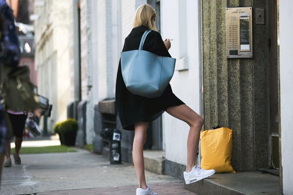 Elegant black jacket, big blue bag and casual white sneakers.
