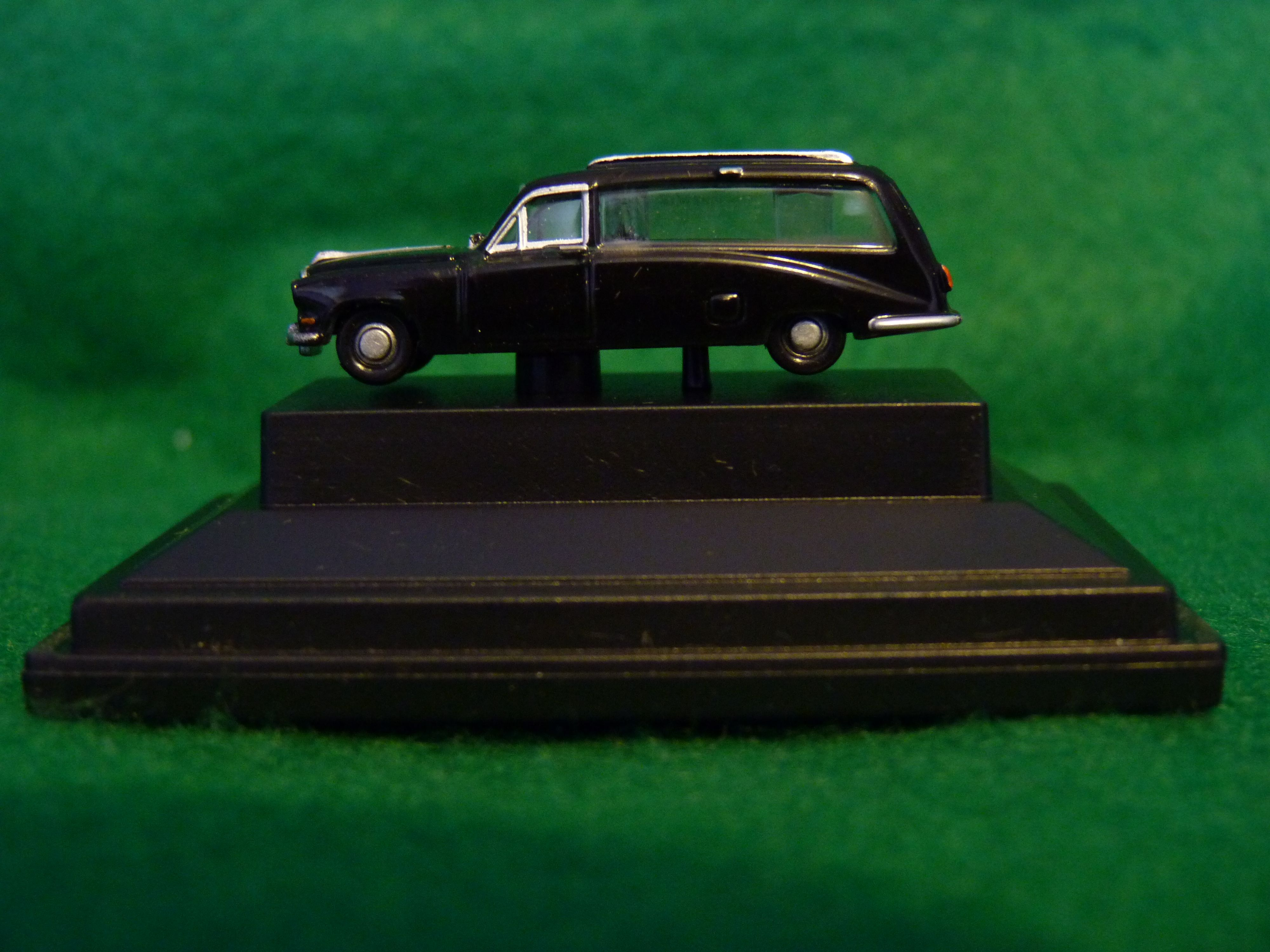 Miniature Model Hearse in Display Case. A tiny piece of the macabre, or perhaps a daily reminder of someone's dream car. The car can be unscrewed from the stand. 3.5cm x 1cm x 1cm.
