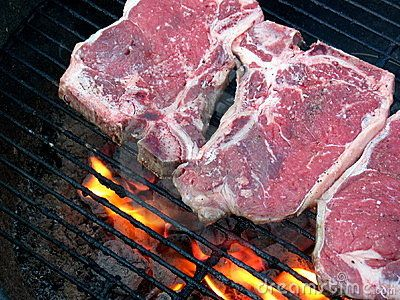 Grilling the T-Bone Steak, with flame and charcoal, just placed, rare.