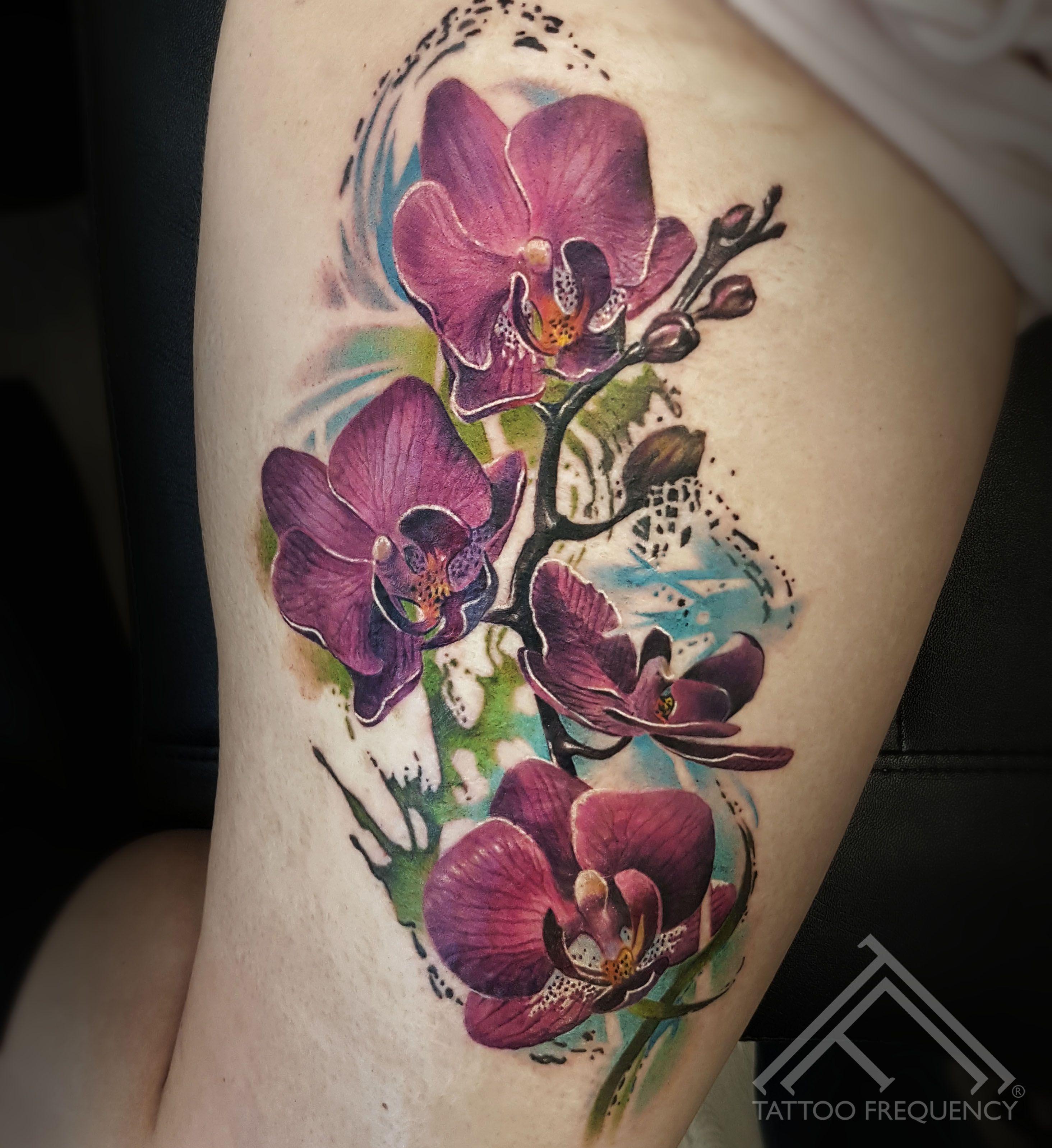Freshly done colorful orchids on womans leg artist maris pavlo