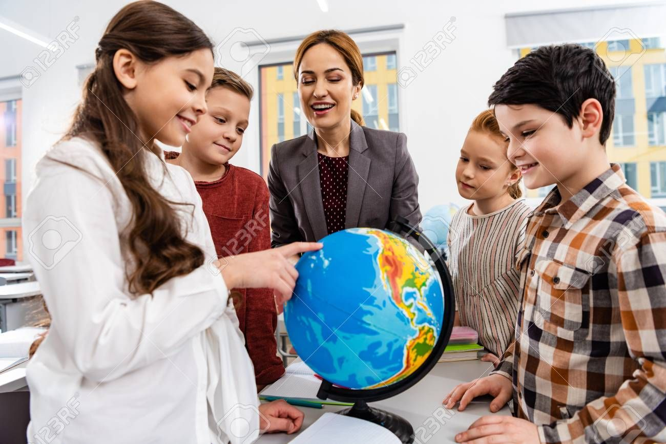 Teacher and pupils looking at globe while studying geography in classroom ,