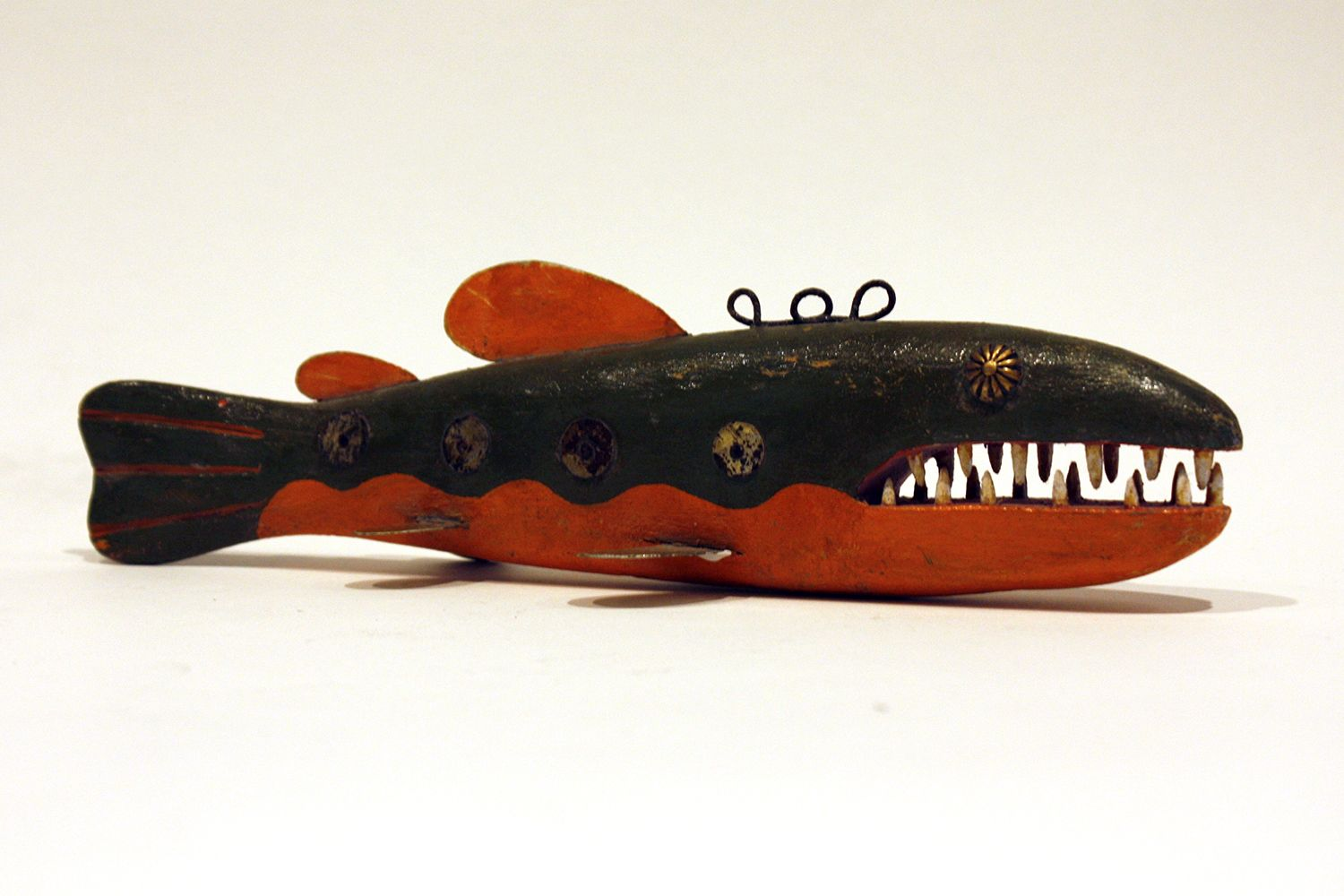 """FISH DECOY/ This handcrafted fish decoy, by Gordon Swenarton, is a colorful, wooden piece. Olive on top with a dark orange belly, the fish is studded with metal fins and """"scales"""" and eyes. Even the sharp-looking white teeth have some intentional discoloration, which speaks to the detailed work of the artist and his high-quality craftsmanship. 10 1/2"""" x 3"""" x 3"""". Photo by Sam Fein"""