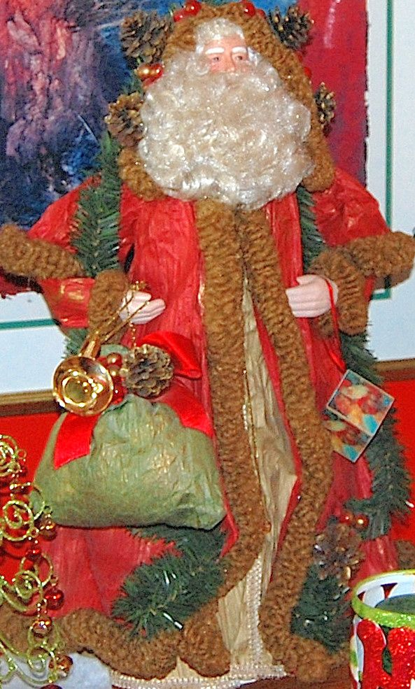 Old St. Nick, Santa made out of crinkled, wrinkled, paper has fake fur trim, gold rope tie, bag of presents and horn. This standing Santa makes a unique Christmas decor