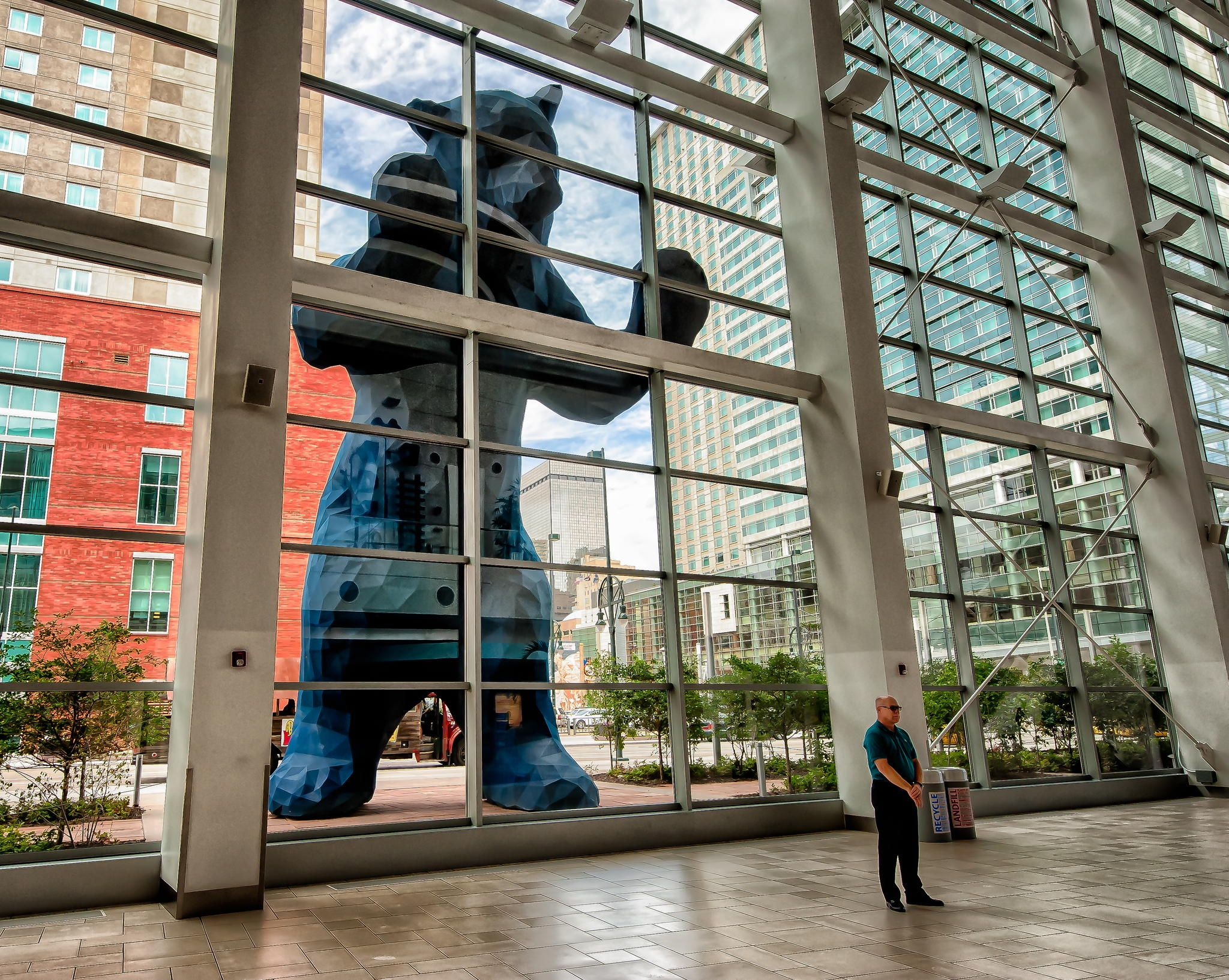 40-foot-tall Blue Bear sculpture outside the Denver Convention Center in Colorado. And despite appearances, the man is not a guard. He is just a tourist posing for a photo of himself in front of it