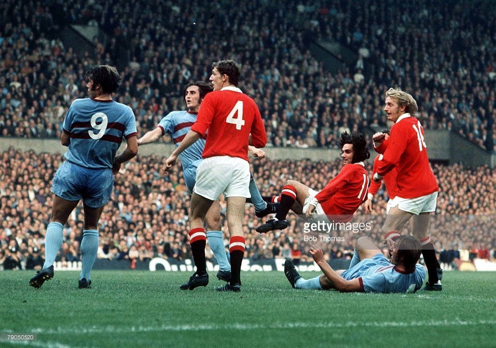 18th September 1971. Manchester United winger George Best acrobatically scores against West Ham at Old Trafford while Hammers Geoff Hurst, Frank Lampard and Billy Bonds are unable to react and Denis Law and Alan Gowling watch on.