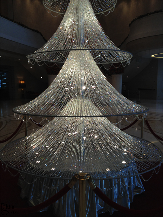 a fifteen foot crystal christmas tree standing under a huge swarovski crystal chandelierin the - Crystal Christmas Tree