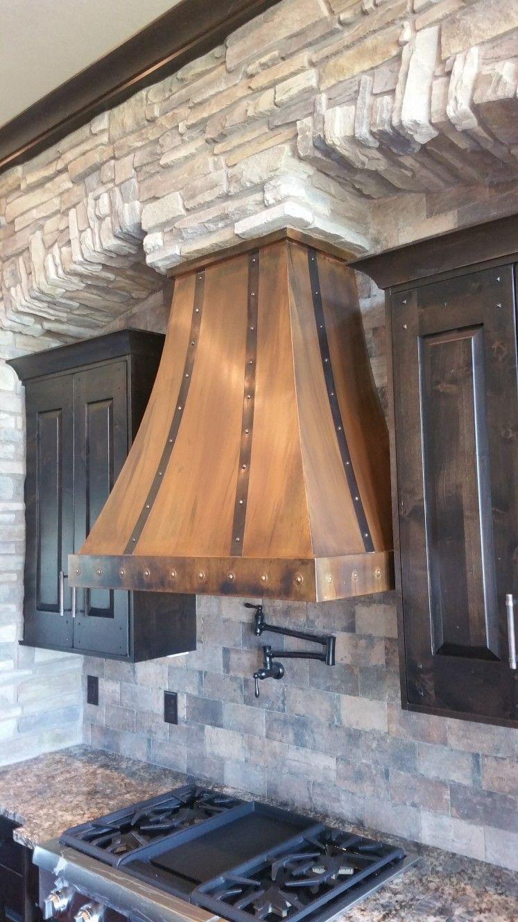 Farmhouse kitchen copper range hood stone fireplace