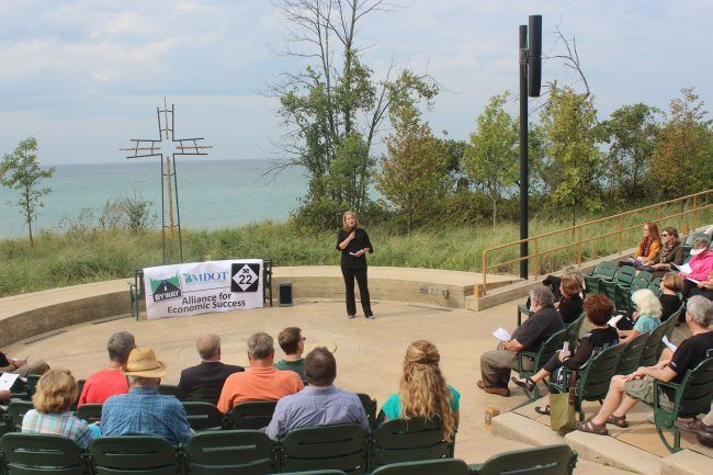 Tamara Buswinka, community development director for the Alliance of Economic, success serves as emcee for the ribbon cutting ceremony for the M-22 Pure Michigan Scenic Byway on Wednesday. (Robert Myers/Pioneer News Network)