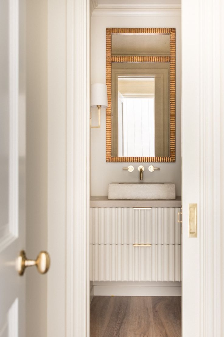 Simple powder bath with gold accents an fluted floating - Preston hardware bathroom vanities ...