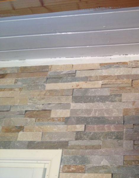 Viimeisen päälle tarkkaa sisustuskiven asettelua seinään. Kaunis yhdistelmänä - valkoinen maalattu katto ja kiviverhoiltu seinä.
