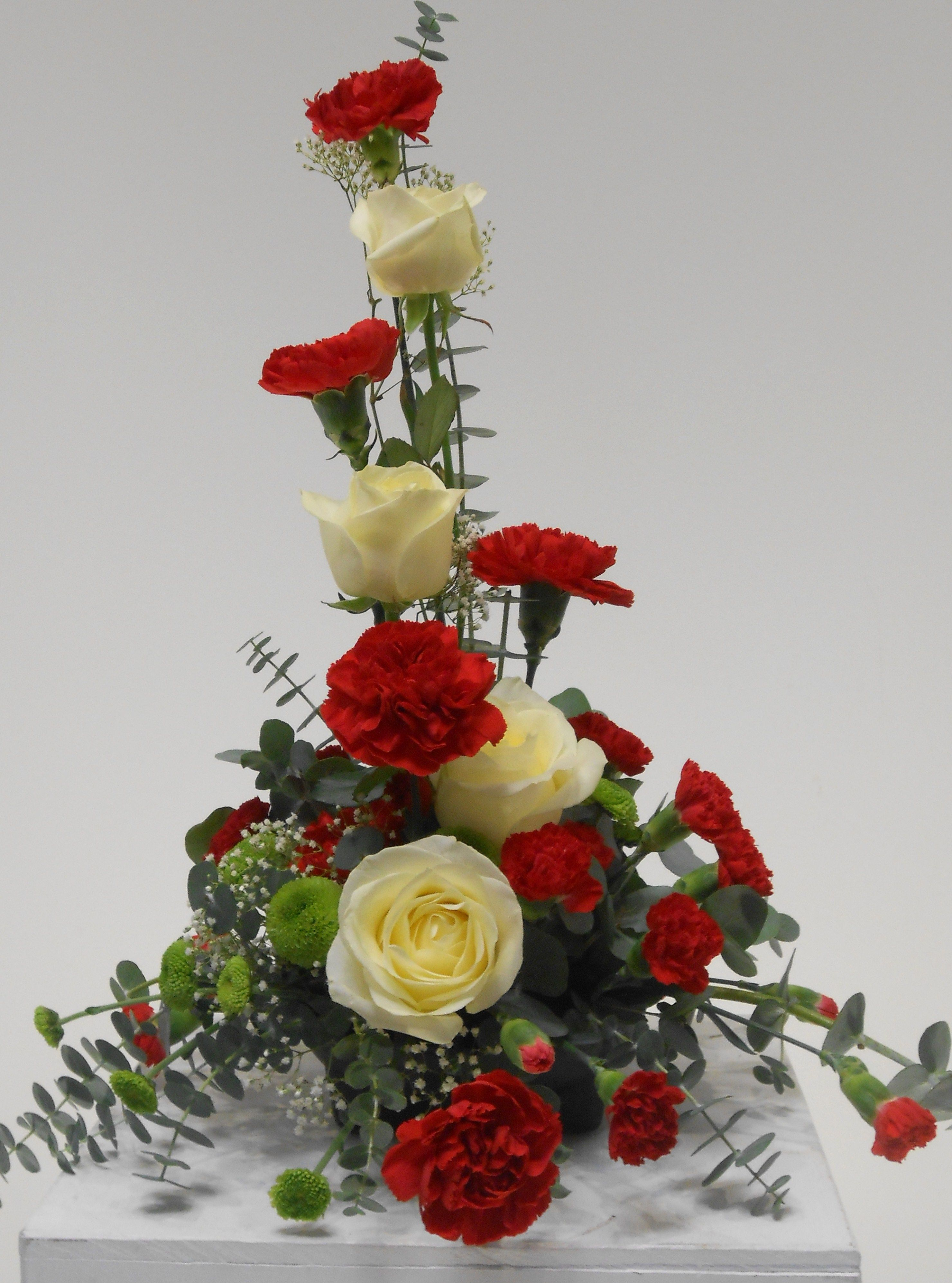 symmetrical front facing arrangement- red carnations, white roses, babys  breath.