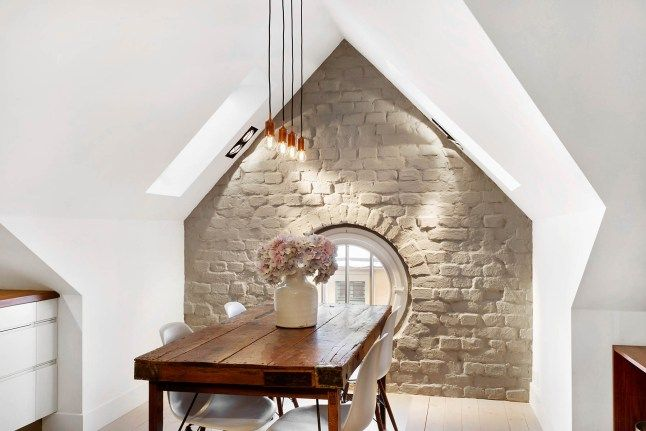 Dining space. Love the stone wall.