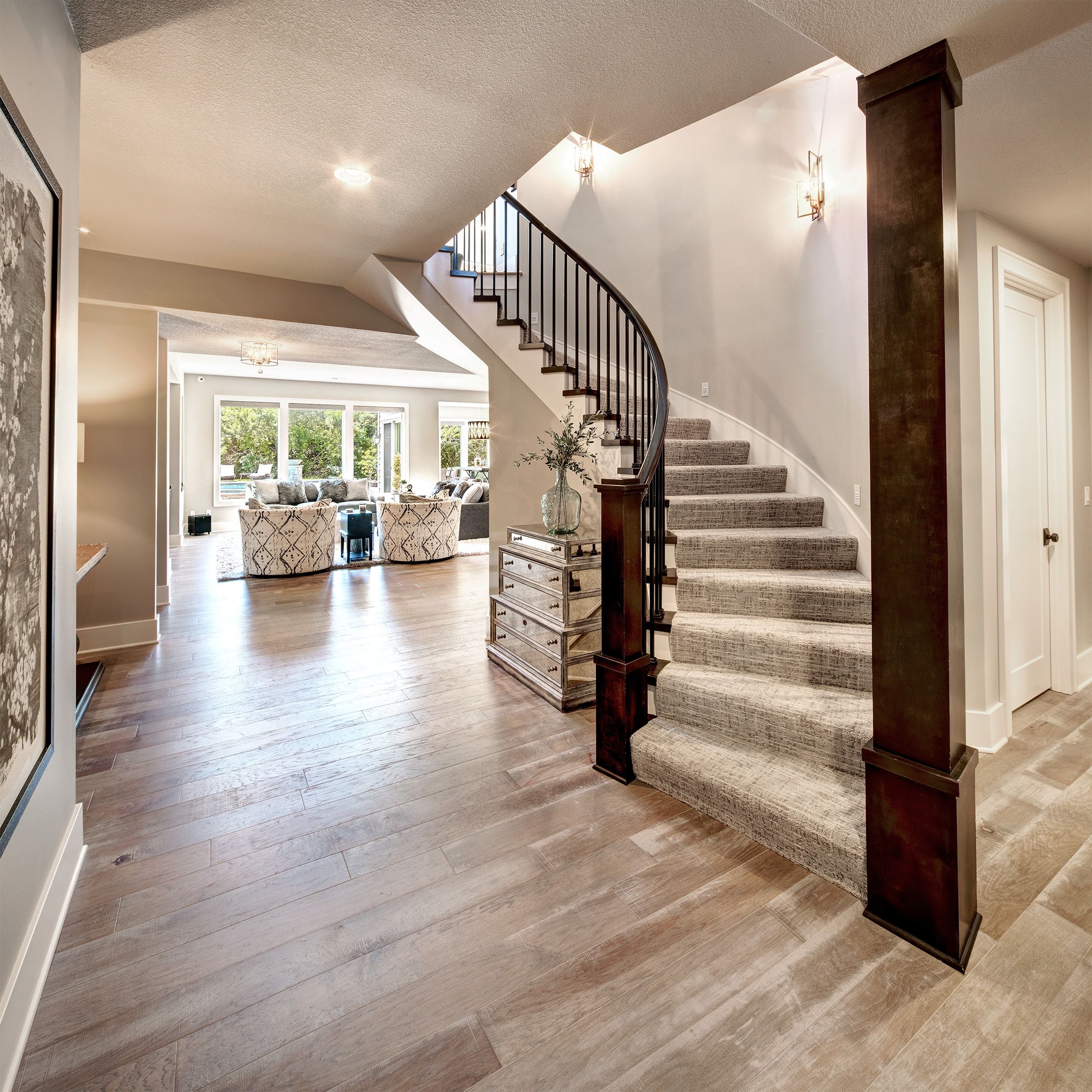 Curved Staircase To Lower Level Open Concept Light Wood Floors Traditional Staircase Wood Floor Stairs Light Wood Floors