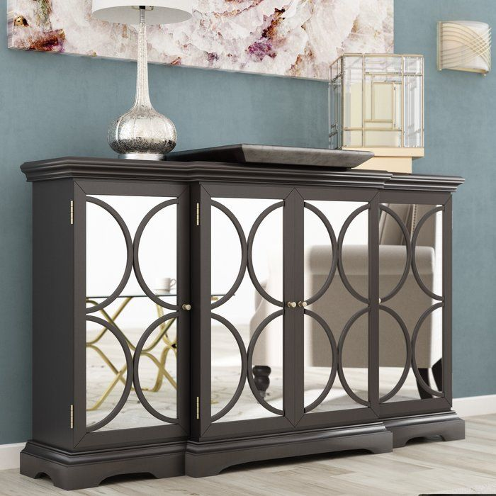 Make a stunning statement while also adding high style to your space with this must-have chest. Crafted of solid woofront of the chest is mirroredd, its clean-lined frame is founded upon a bracket foot base and features a classic black finish. The center of the front pops out for an extra touch of dimension, while it is detailed with shimmering ivory panels and a black circular trellis overlay. Open its four brushed nickel-finished knob-adorned doors to reveal two layers of storage space…