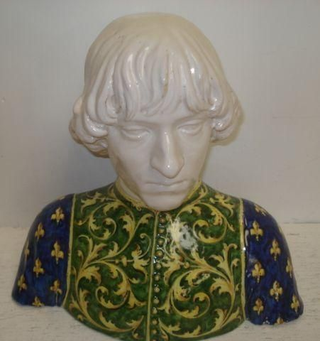 A continental Majolica bust, of a Renaissance nobleman,with cream glazed head and wearing a yellow and green scroll jerkin with fleur de lys painted sleeves, 30cm.