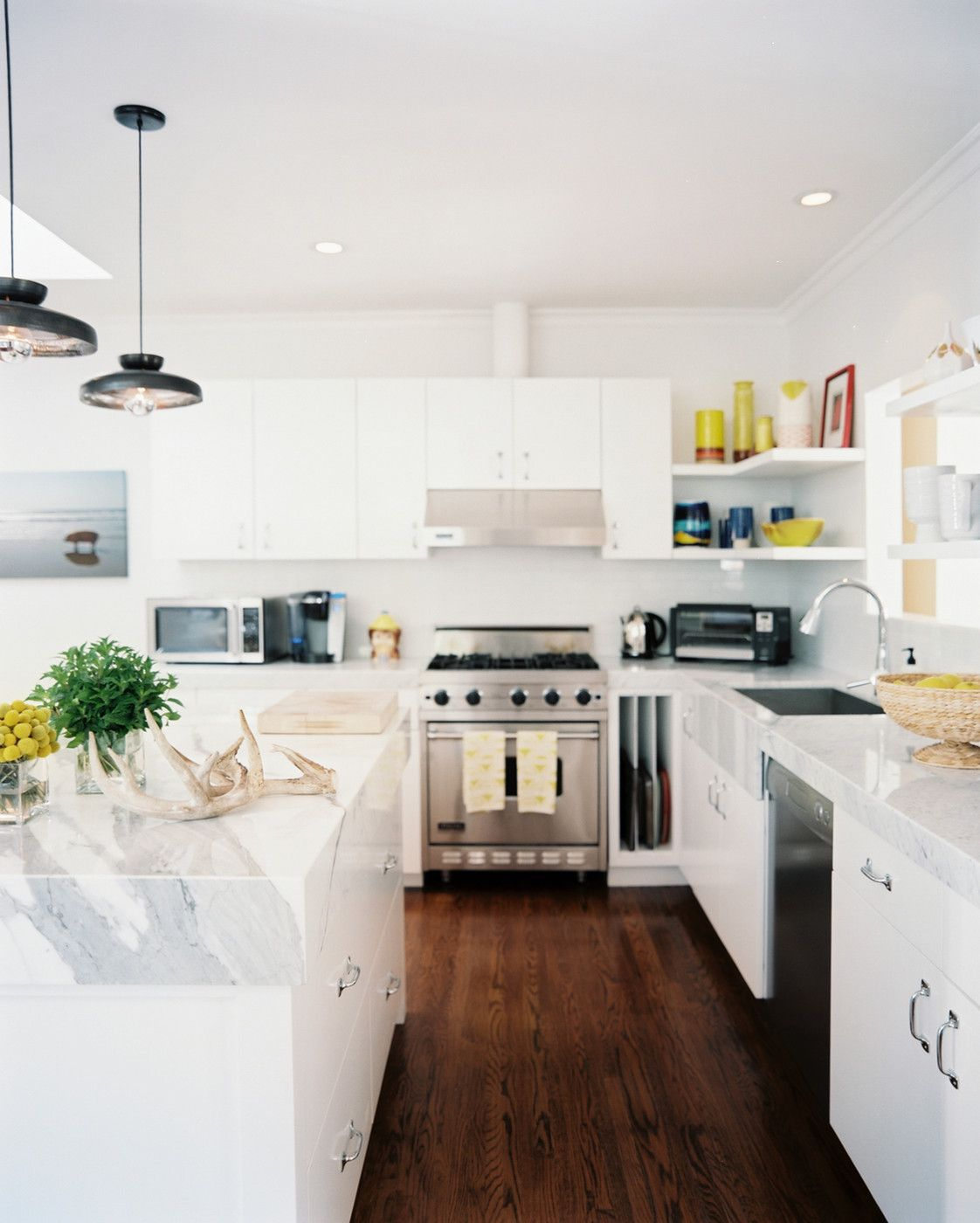 Marble countertops and white cabinetry in a bright kitchen.