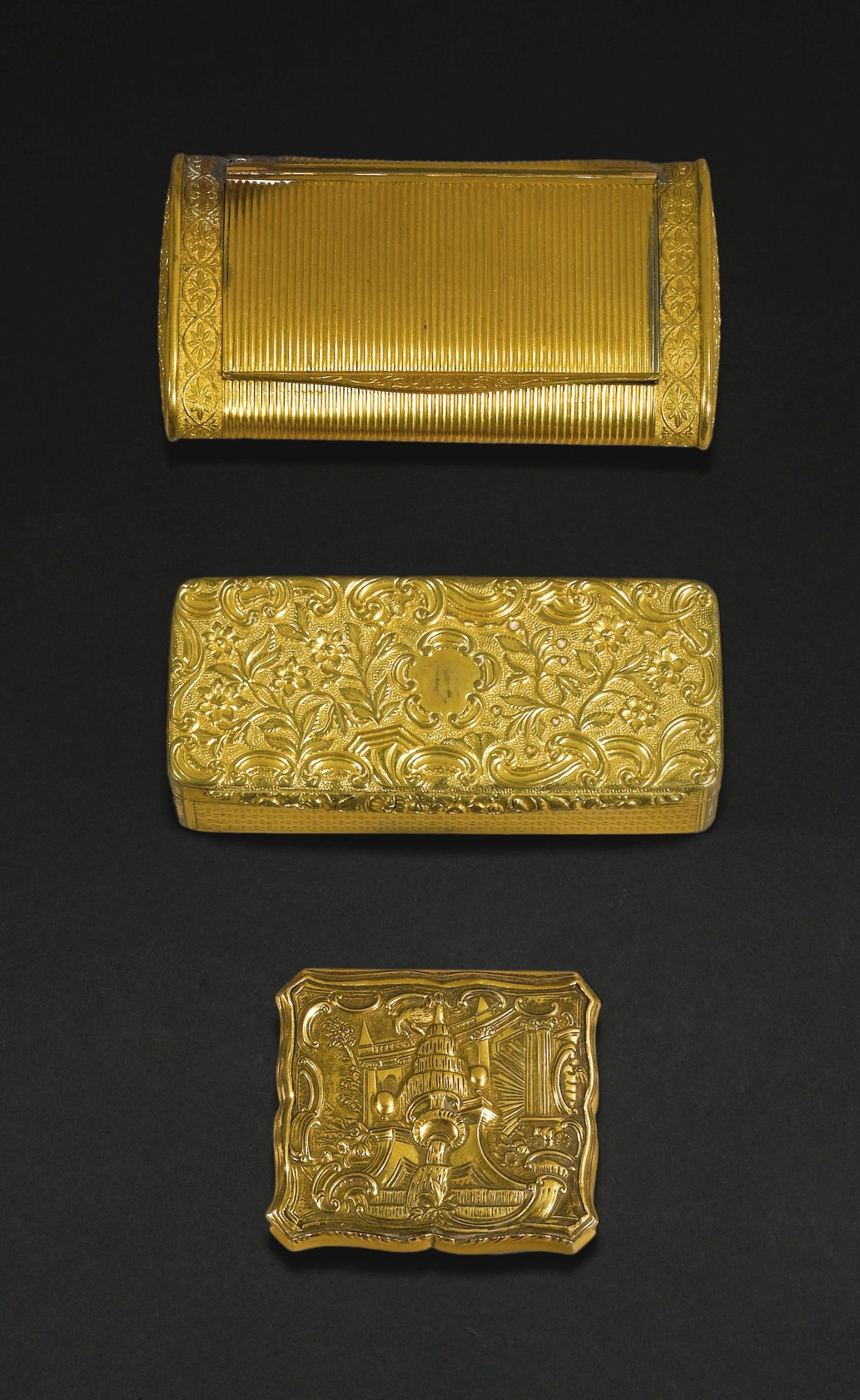 A small gold patch box, English or German, mid 18th century of shaped rectangular form, the lid chased with a rococo fountain, mirror-lined, later French control marks, 4.7 cm., 1 1/2 in.; a doublé snuff box, rectangular, oval section, reeded within neo-classical borders, lid interior with later Crewe monogram below an Earl's coronet and inscribed: Rue for remembrance, maker's mark rubbed, 16th gold quantity, circa 1825; and an oblong engine-turned gilt-metal snuff box with flowered lid and…