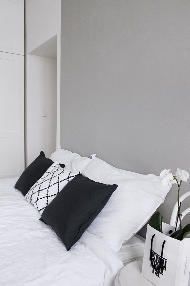 Grey Scandinavian bedroom with the white linen sheets, Ton chair, Diptyque, white orchid and abstract painting made by Ma Maison Blanche