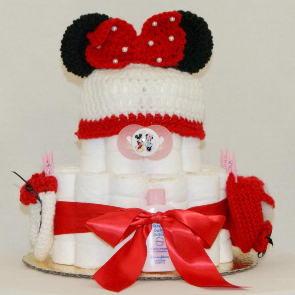 : 27 Premium quality Pampers (size 1), Hand made red Minnie Mouse hat, mittens, booties, bottle and matching binkie. Johnson and Johnson's baby soap, shampoo, lotion and Desitin creme. Embellished with baby cloths pins and matching ribbon. Our cakes do not fall apart, we guarantee satisfaction! To customize your cake contact us on Facebook/Keepsake Diaper Cakes.