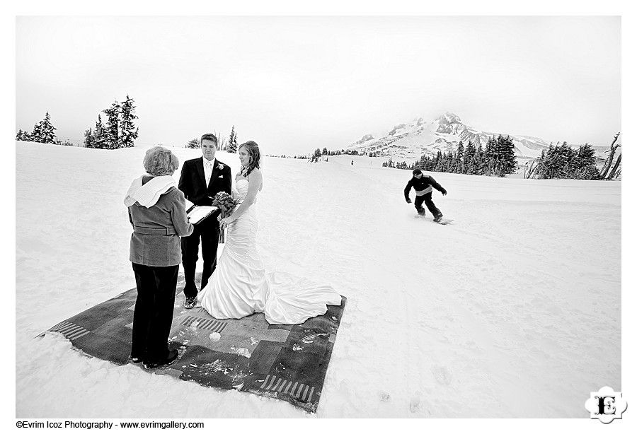 A snowboarder passes by this bride and groom's wedding ceremony at Timberline Lodge