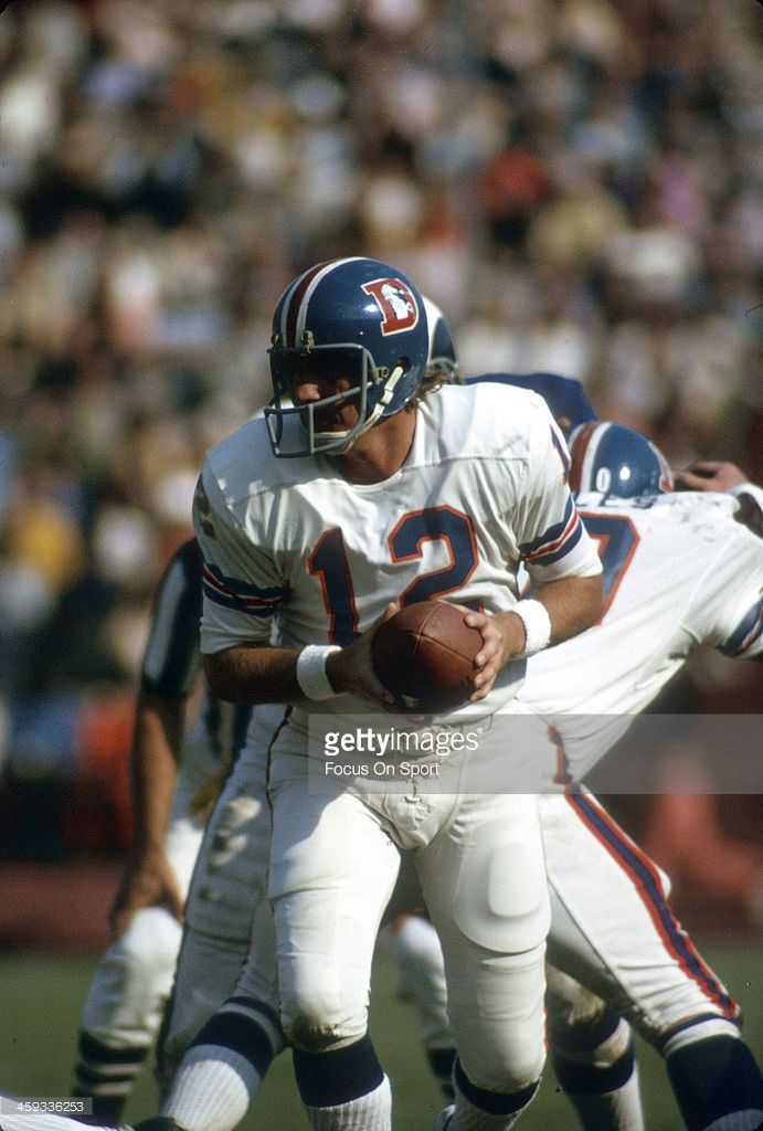 Charlie Johnson #12 of the Denver Broncos turns to hand the ball off against the Los Angeles Rams  1974 . Johnson played for the Broncos from 1972-75.