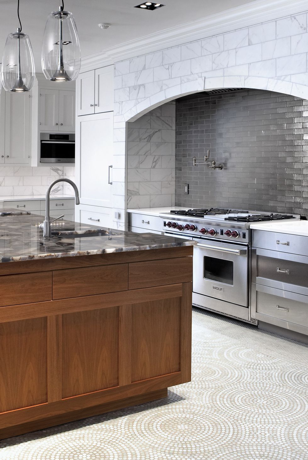 A mosaic floor paired with marble countertops and two different tile styles creates a chic melange of patterns in this contemporary kitchen