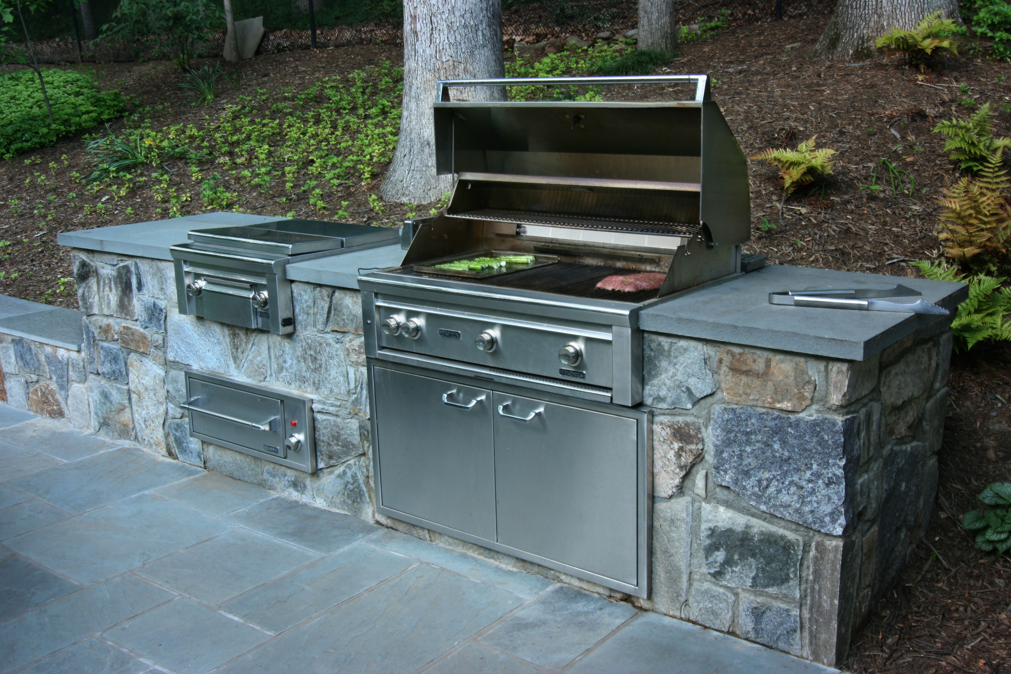 In This Woodland Hillside Setting A Retaining Wall Does Double Duty As A Built In Grill And Warming Draw Outdoor Kitchen Patio Built In Grill Outdoor Kitchen