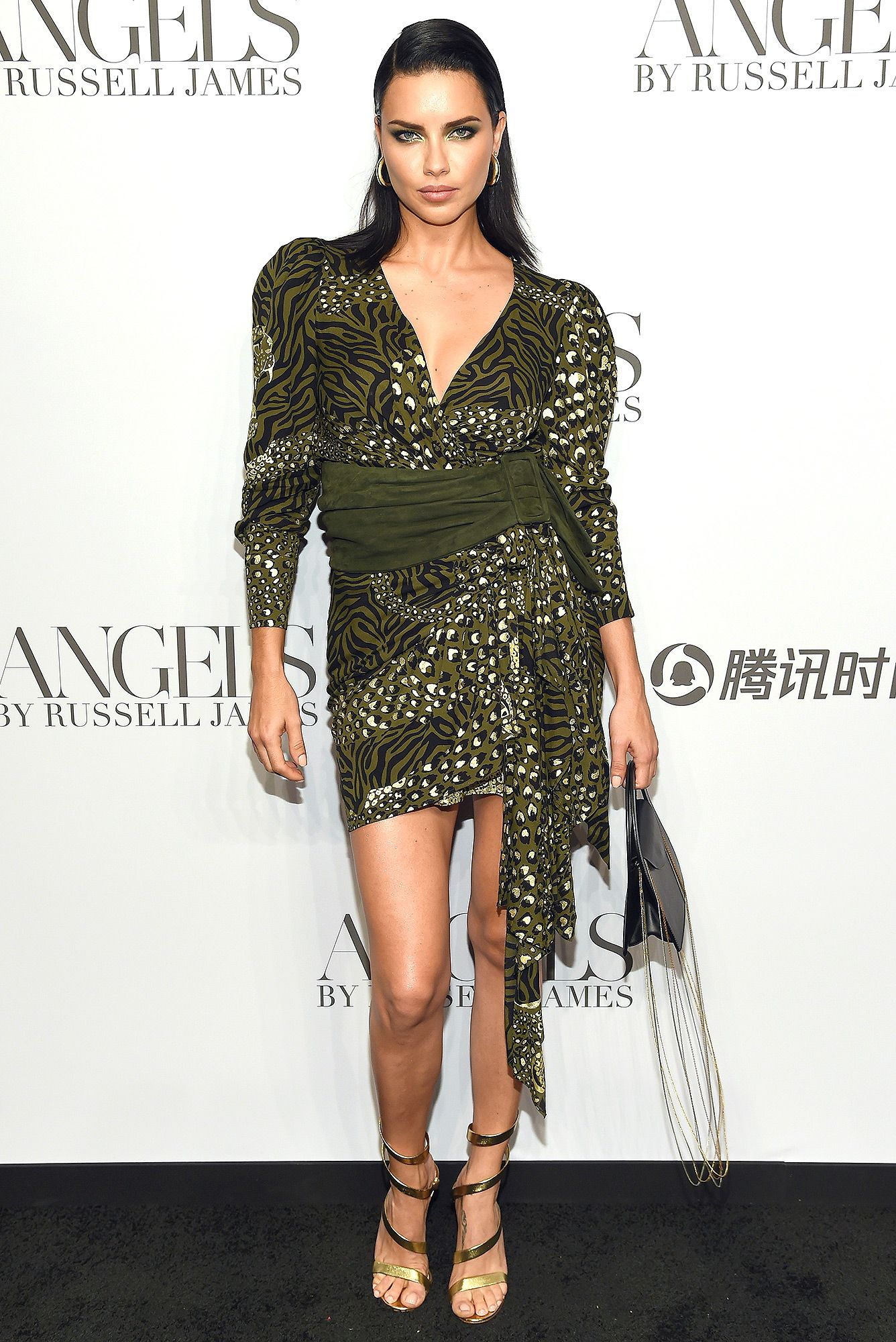 Adriana Lima wears an olive green leopard-print mini dress and ankle-wrap  gold sandals at the ANGELS by Russell James book launch and exhibit in  N.Y.C. e386abf72