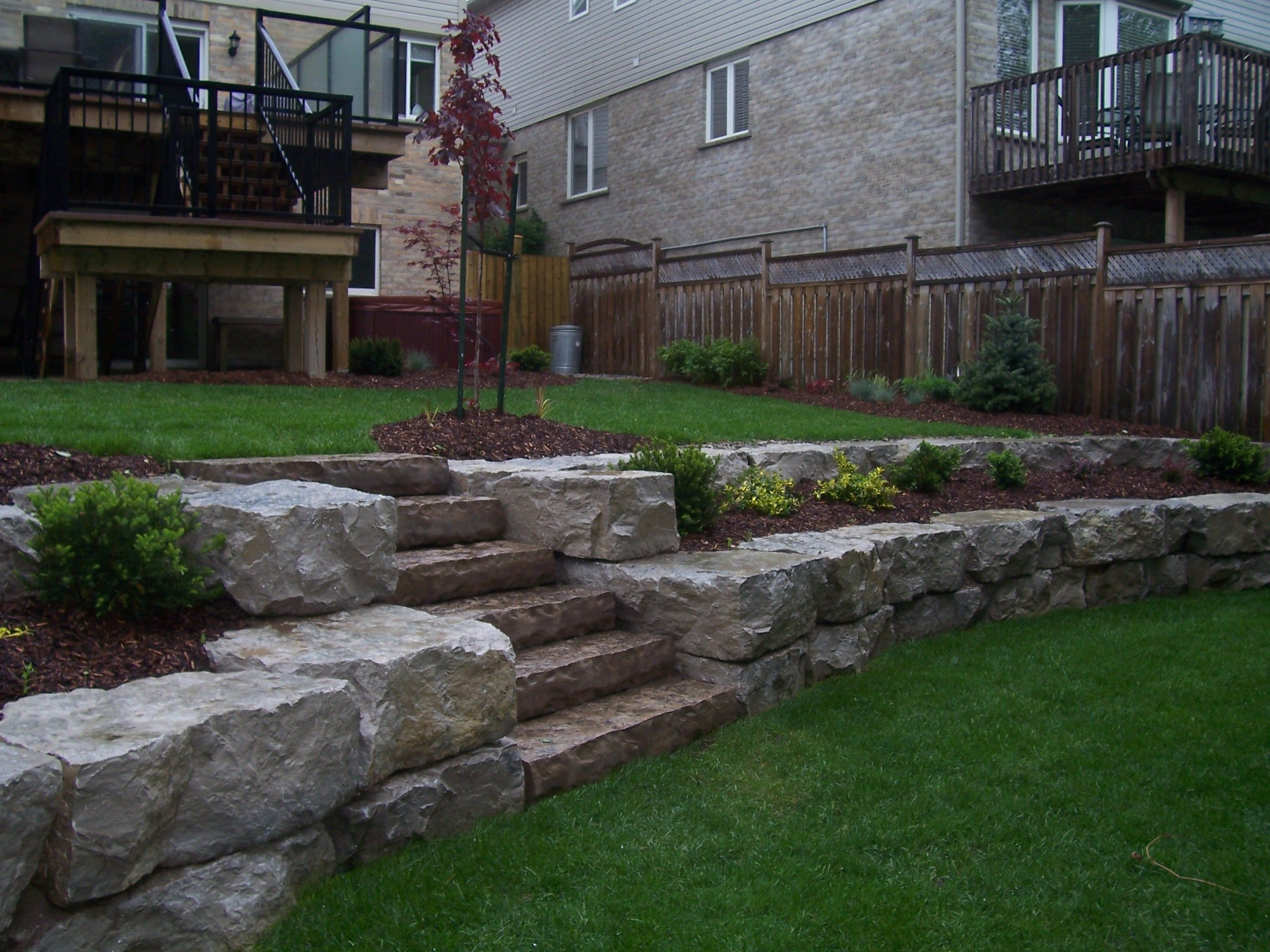 Backyard multi-level stone wall and flowerbeds feature ... on 2 Level Backyard Ideas id=47410