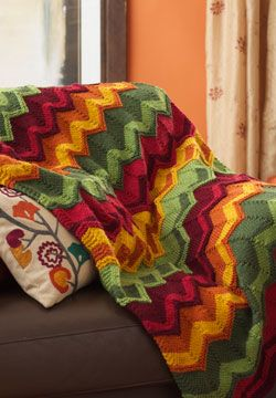 Bold chevron stripes knit in spicy shades make this blanket a great way to add warmth a home. Shown in Patons Canadiana. Free pattern.