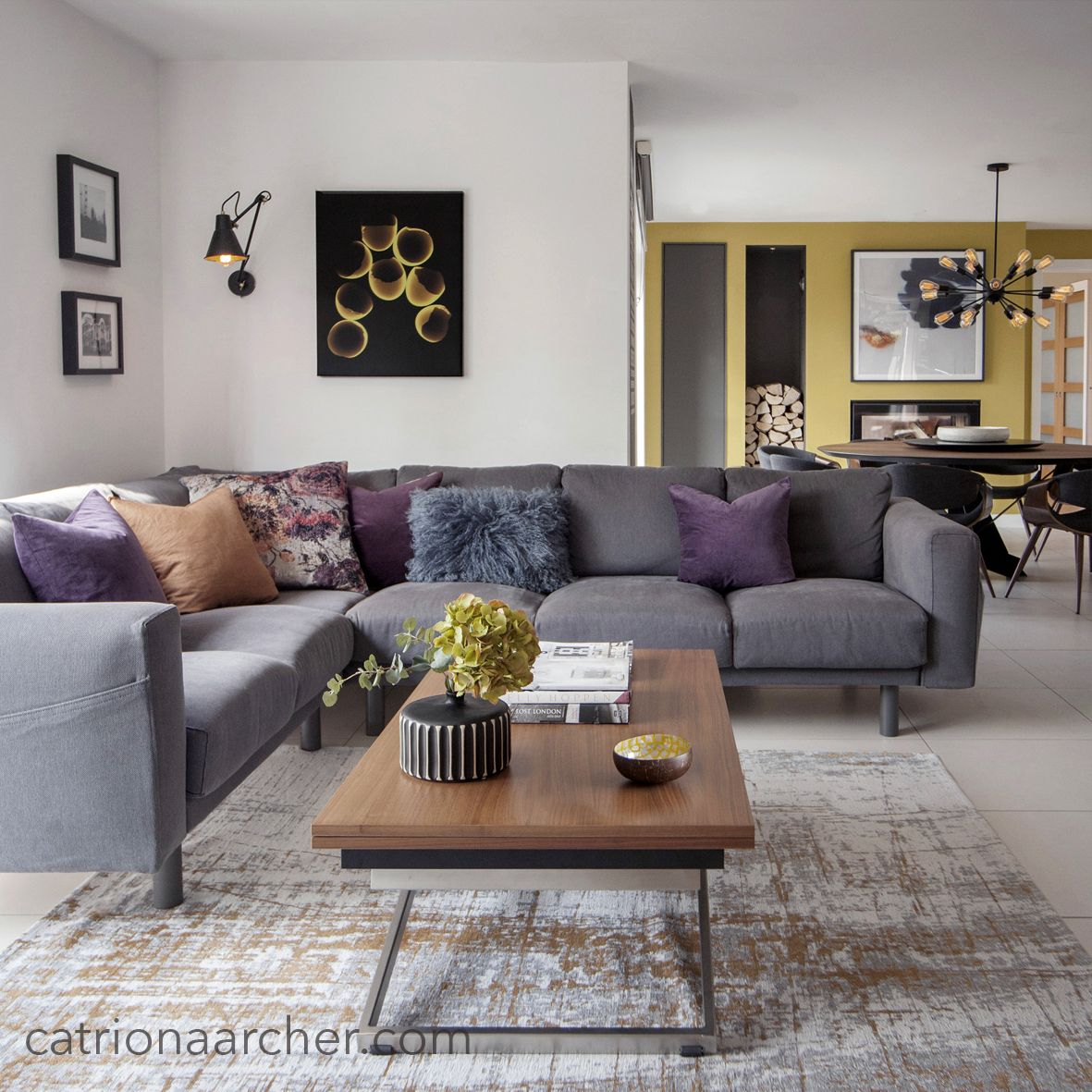 Open plan sitting room with grey, rust terracotta and purple