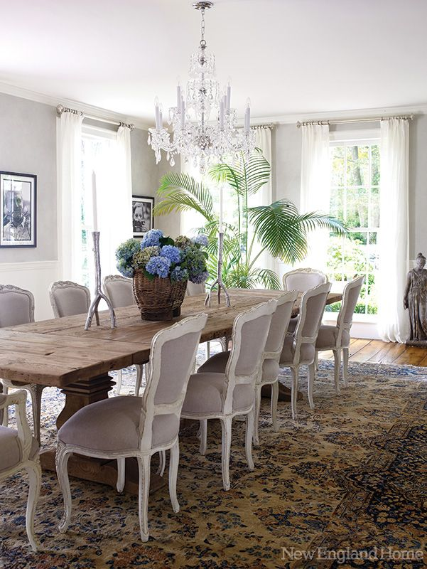 The Rustic Dining Table Gets Dressed Up With Nineth Century Louis Xv Style Chairs Upholstered In Gray Linen A Chinese Rug And Voile Curtains Contribute