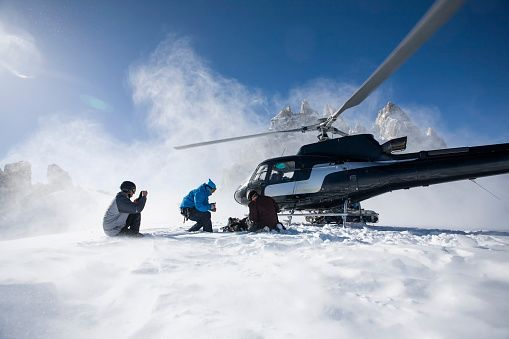 Stock Photo : Three male snowboarders exiting helicopter, Trient, Swiss Alps, Switzerland