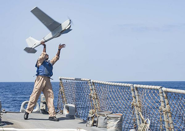 Petty Officer 3rd Class Dale Young launches an RQ-20A Puma AE (All Environment) unmanned aircraft system from the flight deck of the guided-missile destroyer USS Stout (DDG 55).
