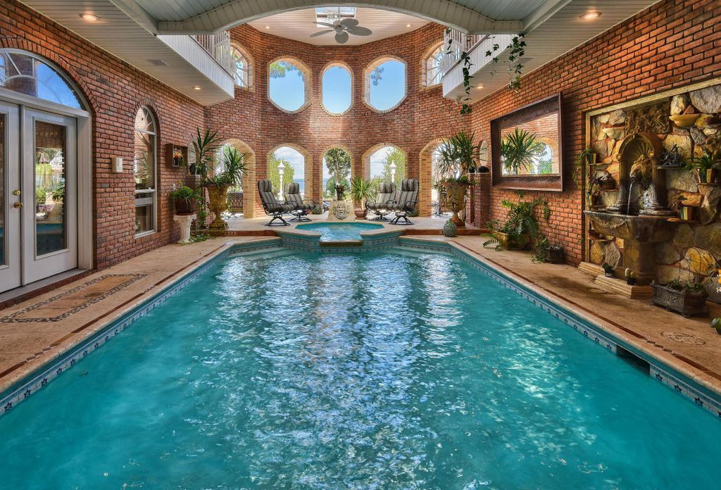 Traditional Swimming Pool with Fence, exterior tile floors, Fountain, Pool with hot tub, Skylight, Indoor pool