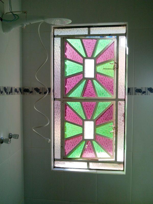 Janela vitral antiga dá um charme especial ao banheiro.