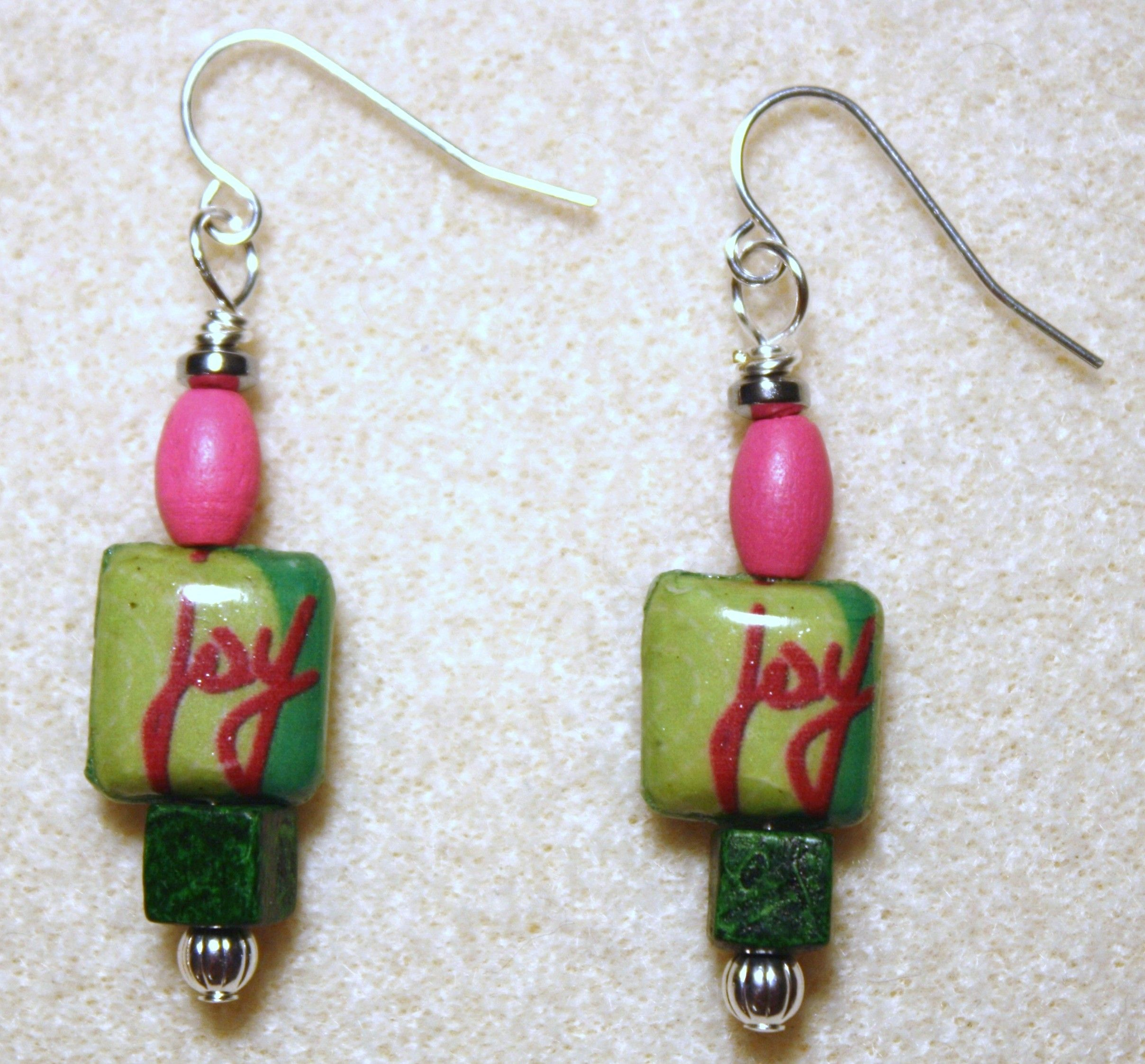 "Handcrafted by Teal Palmetto, LLC. Are you a joyful person, or do you know someone who is?  This pair of earrings fits the bill!  Decoupaged ""joy"" beads combine with wood and ceramic beads in shades of pink and green.  Silver metal accent beads and silver fish hook ear wires complete the look.  Price: $12."