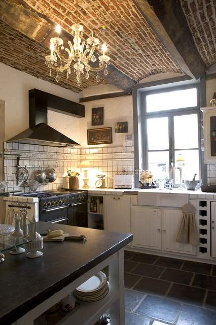 Rustic kitchen. I love the details like the bare cabinet next to the stove and underneath the island. I also like the brick and beam ceiling.