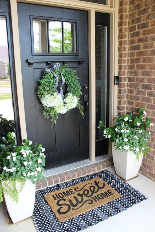 Make your front porch look beautiful by adding a pop of color with plants! #frontporchideas #curbappeal #blackfrontdoor #popsofcolor