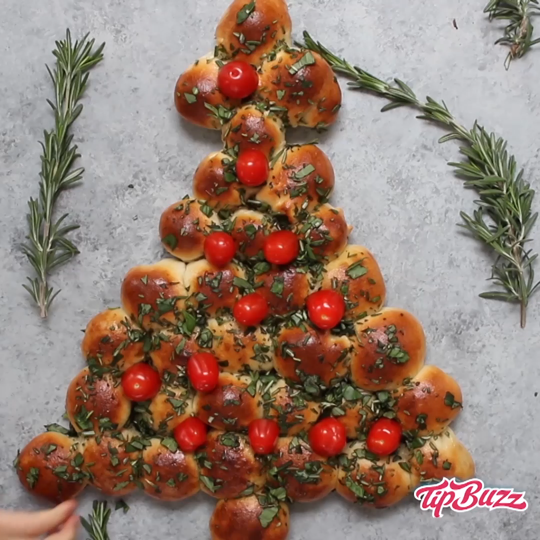 Christmas Tree Pull Apart is a delicious appetizer recipe made with a few simple ingredients: biscuit dough, butter, fresh herbs and cherry tomatoes. It's perfectly easy and festive to make for a holiday party and a great way to wow your guests! Party recipe. Snack recipe. Holidays. #appetizersforparty