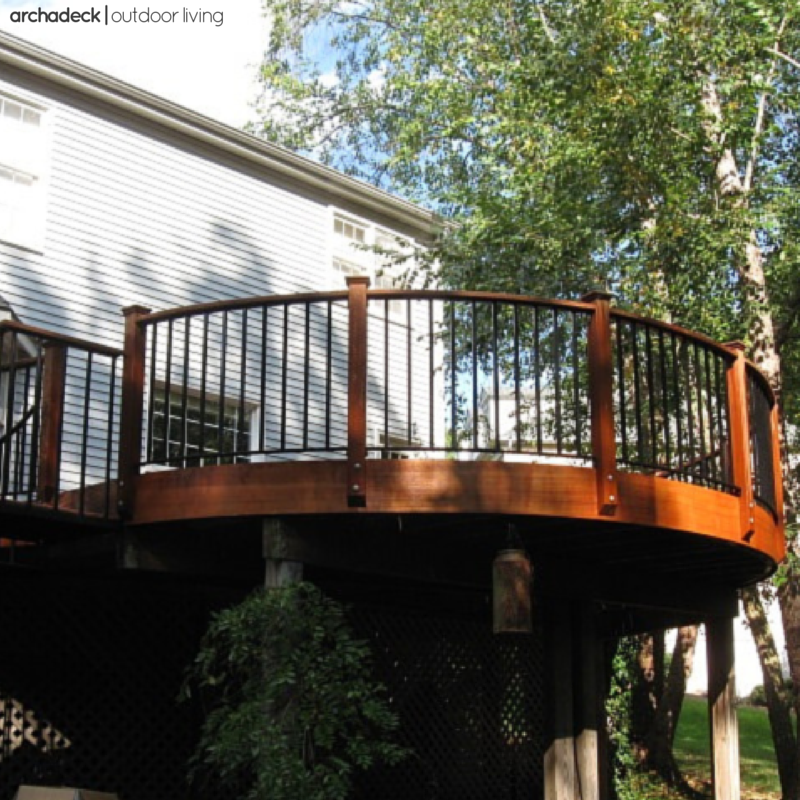 Curves, as a prominent design feature, are beautifully incorporated into this elevated hardwood deck with metal rails.