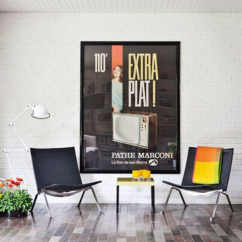 interiors, living room, vintage poster print. love the pops of orange and yellow with black and white.