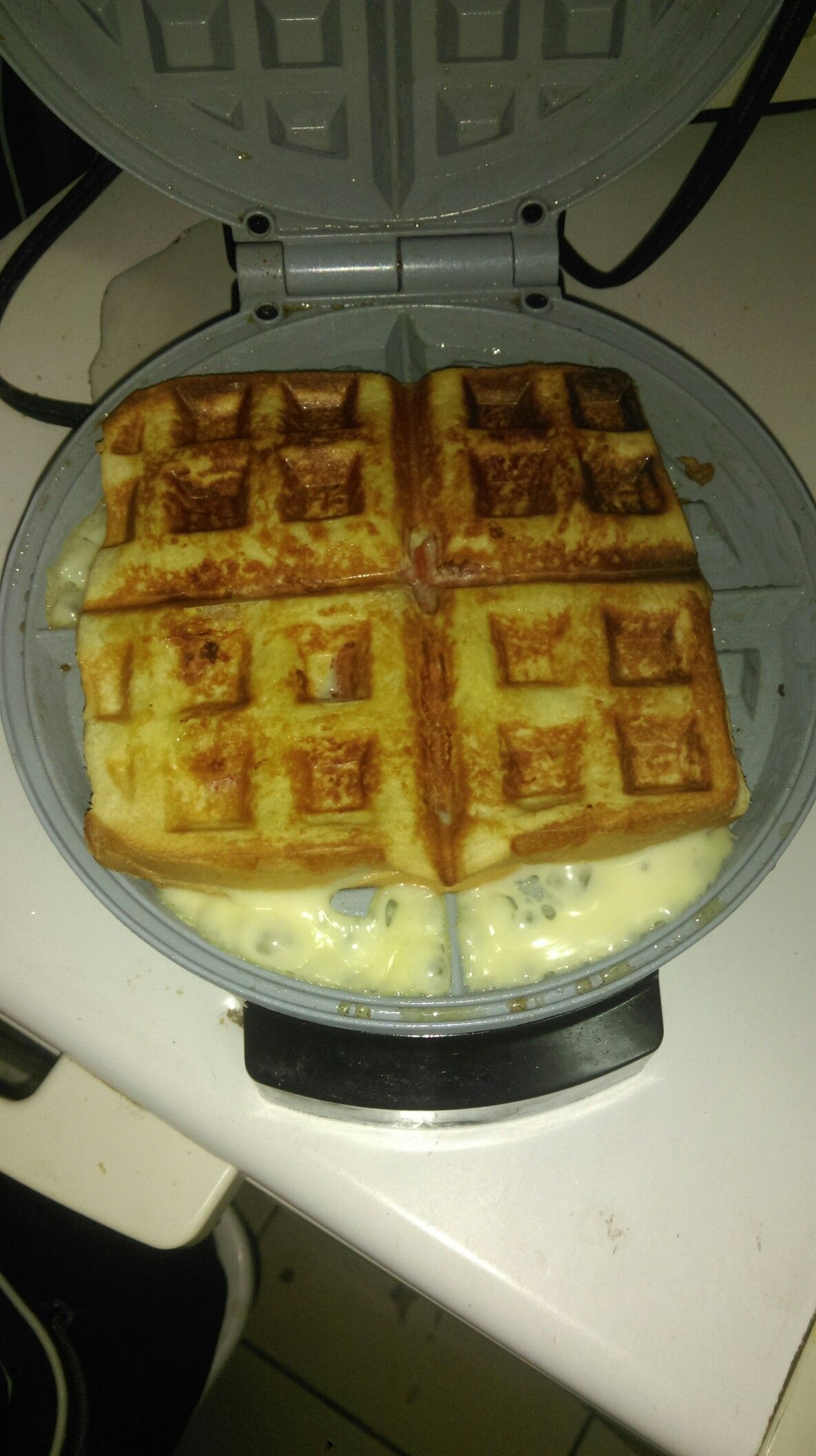 Bread, egg, sausages and cheese in a waffle maker.