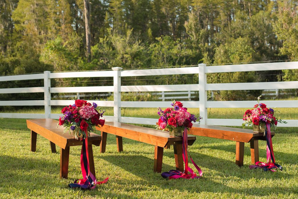 Outdoor Rustic Wedding Ceremony Decor With Wooden Benches, And Small Red,  Purple, And Magenta Flowers With Pink And Purple Ribbon | Tampa Bay, ...