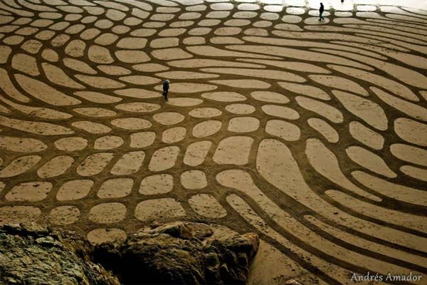 By raking up the wet sand at low tide, he is able to make contrasting sand colors.