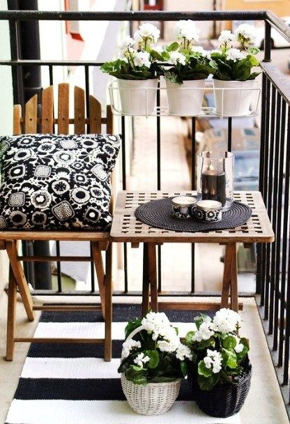 Jugando con el blanco y el negro se ha creado un ambiente chic y moderno, una silla y una mesa de madera ambas plegables con unas plantas es todo lo que necesitas.