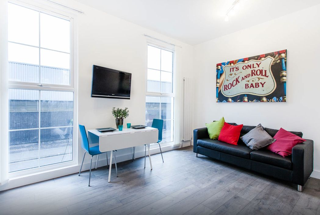 Modern style for this central London flat, close to Camden. Clean white walls with a splash of colour with blue chairs, brightly coloured cushions and a Vegas-design canvas.
